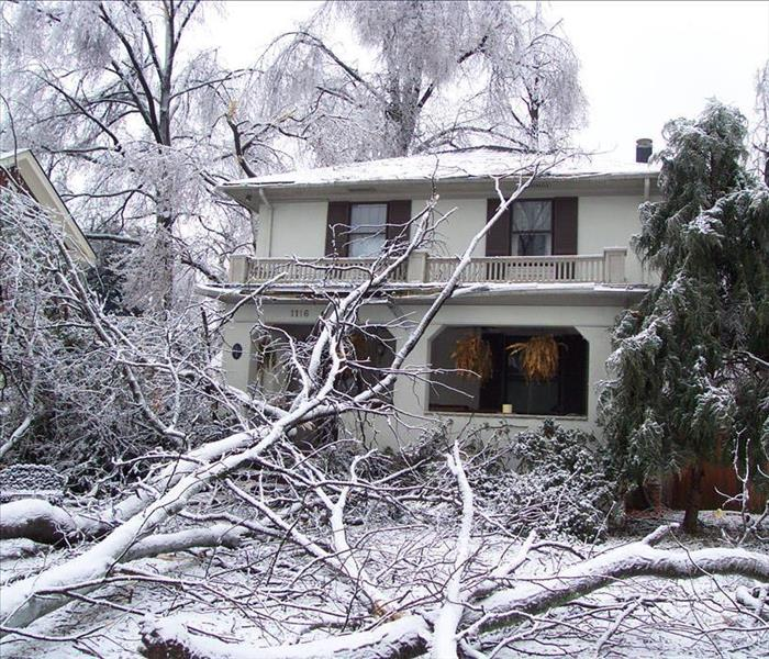 A medium sized tree feel down on the porch of a two story house due to a winter storm.