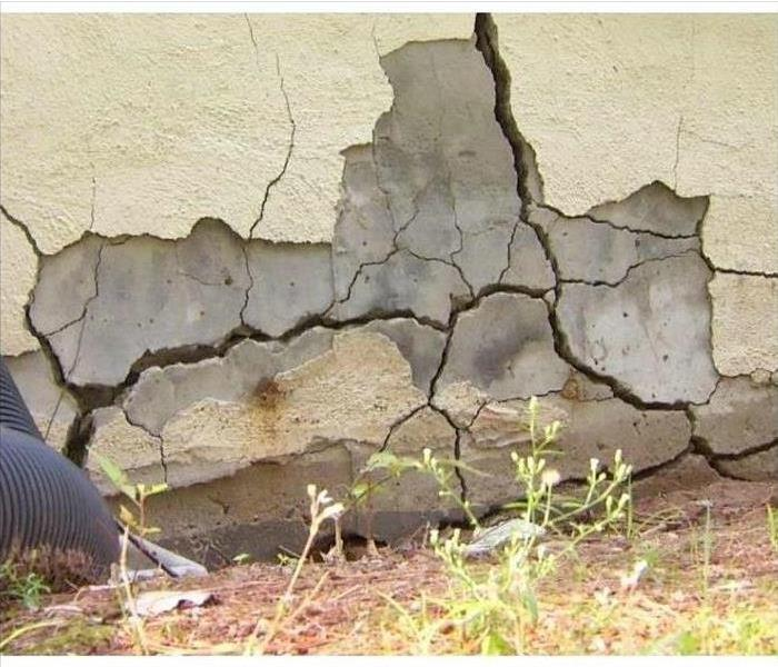 A large and splintering crack in the foundation of a home with someone inspecting it from off picture.